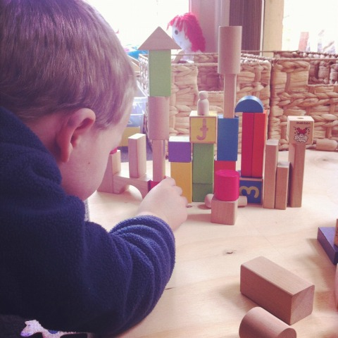 building with blocks and wooden people - An Everyday Story